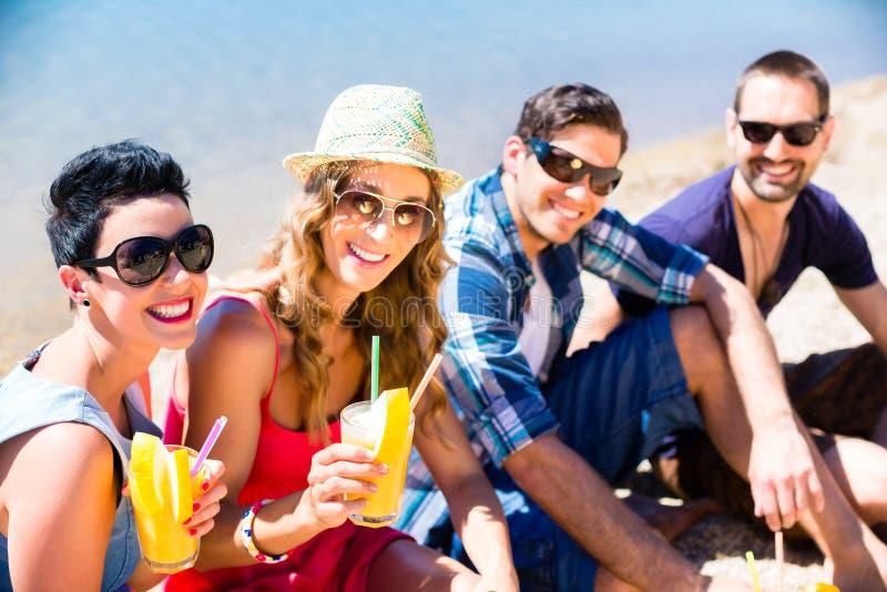 Cuatro amigos que se sientan en la playa del lago con los cócteles imagenes de archivo