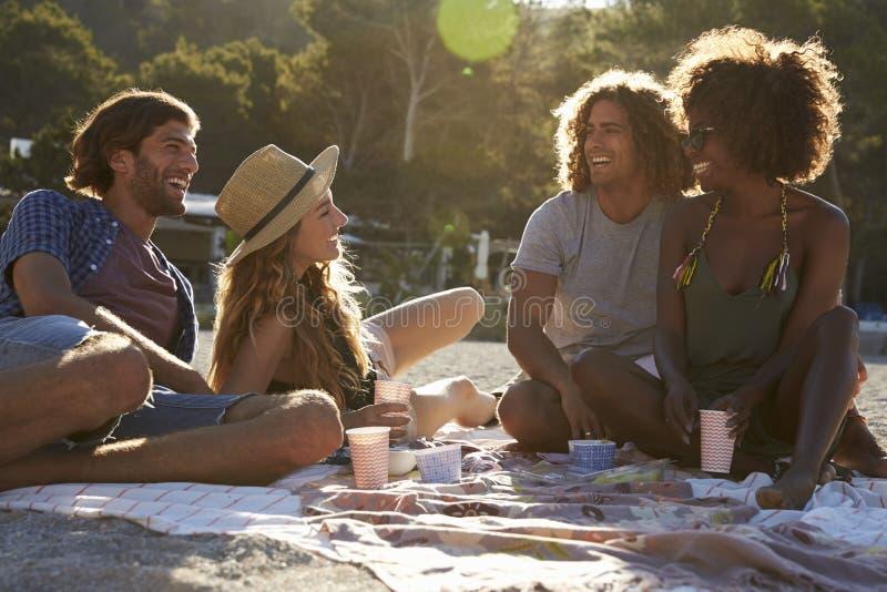 Cuatro amigos que tienen una comida campestre en la playa, llamarada de la lente, Ibiza fotos de archivo