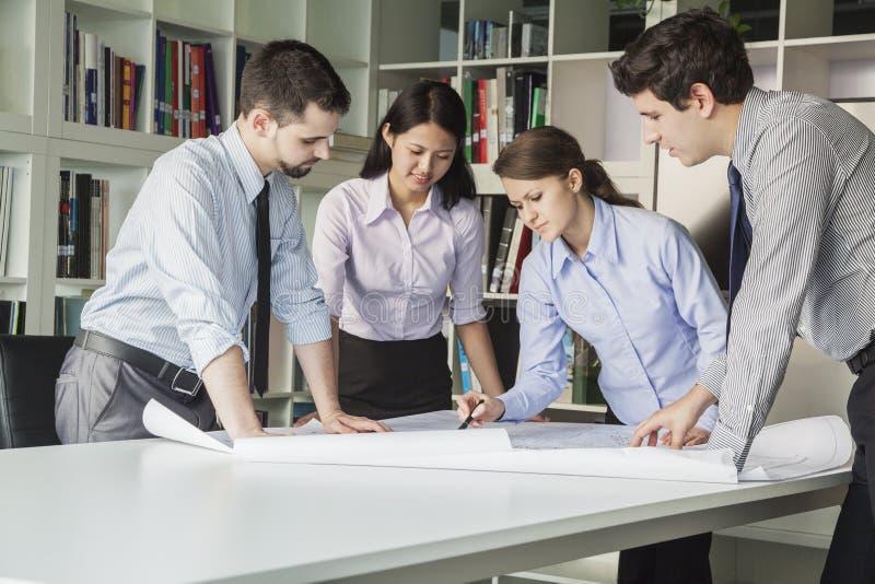 Cuatro arquitectos que se colocan y que planean alrededor de una tabla mientras que mira abajo el modelo foto de archivo