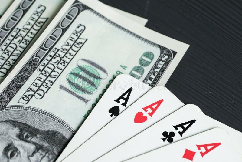 Cuatro as con los dólares americanos mienten en un fondo de madera negro fotografía de archivo