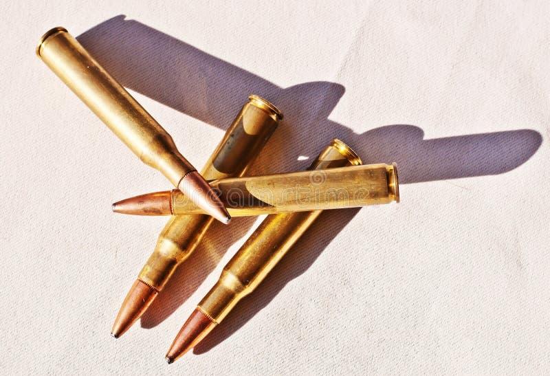 Cuatro 30 06 balas del calibre en un fondo blanco fotografía de archivo libre de regalías