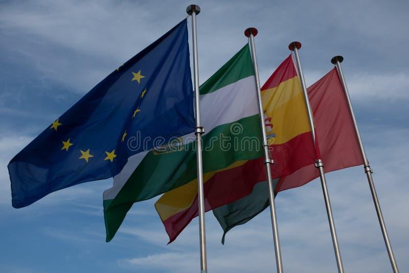 Cuatro banderas que agitan en el viento son las banderas de la unión europea, de España, de Granada y de Andalucía fotografía de archivo libre de regalías