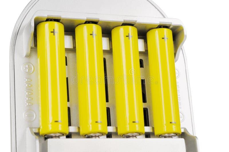 Cuatro baterías en el cargador imagen de archivo