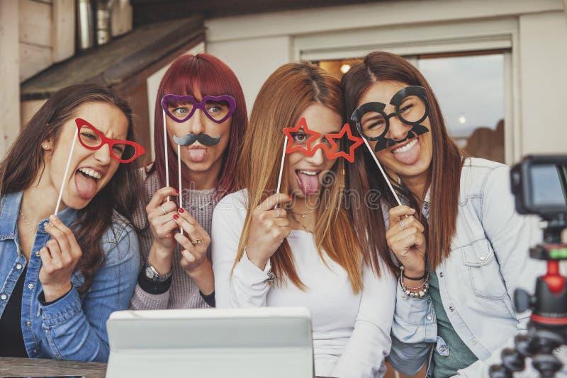 Cuatro bloggers femeninos jovenes se divierten delante de la cámara imagen de archivo libre de regalías