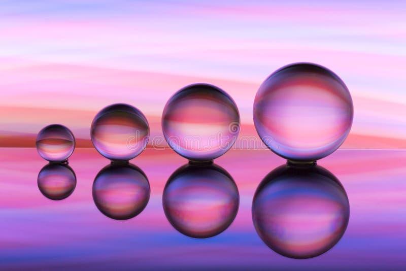 Cuatro bolas de cristal en fila con las rayas coloridas del color del arco iris detrás de ellas fotos de archivo
