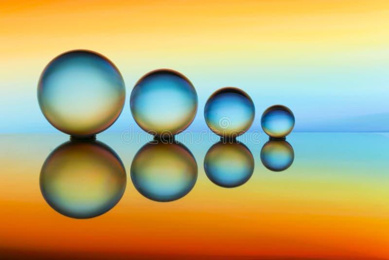 Cuatro bolas de cristal en fila con las rayas coloridas del color del arco iris detrás de ellas imagen de archivo libre de regalías