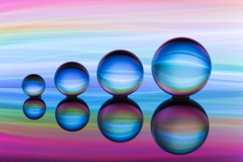 Cuatro bolas de cristal en fila con las rayas coloridas del color del arco iris detrás de ellas imagenes de archivo