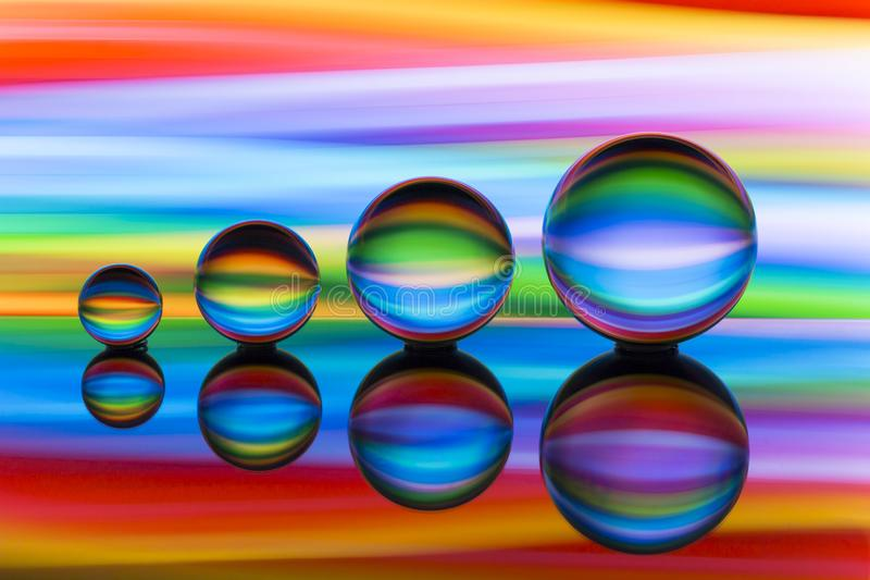 Cuatro bolas de cristal en fila con las rayas coloridas del color del arco iris detrás de ellas fotografía de archivo