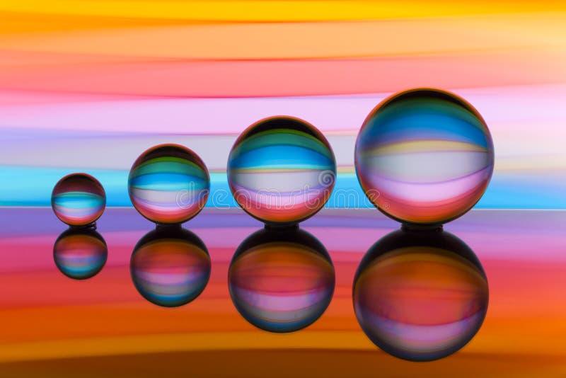 Cuatro bolas de cristal en fila con las rayas coloridas del color del arco iris detrás de ellas foto de archivo