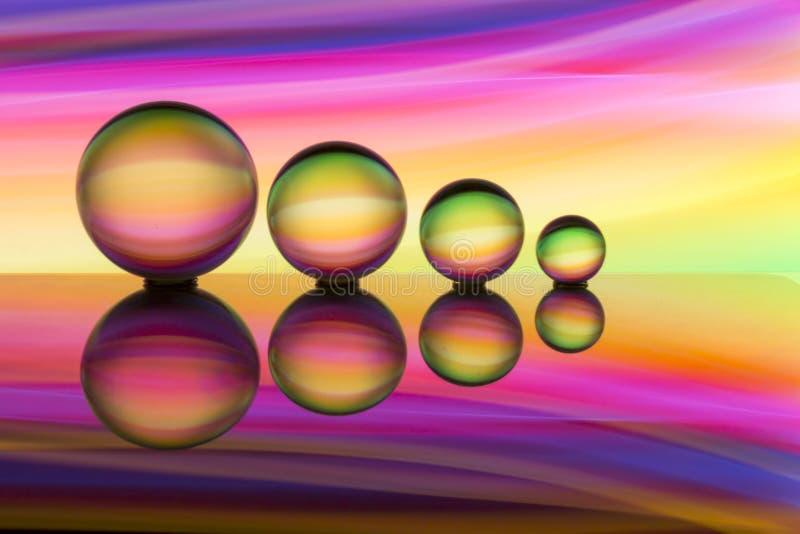 Cuatro bolas de cristal en fila con las rayas coloridas del color del arco iris detrás de ellas fotos de archivo libres de regalías