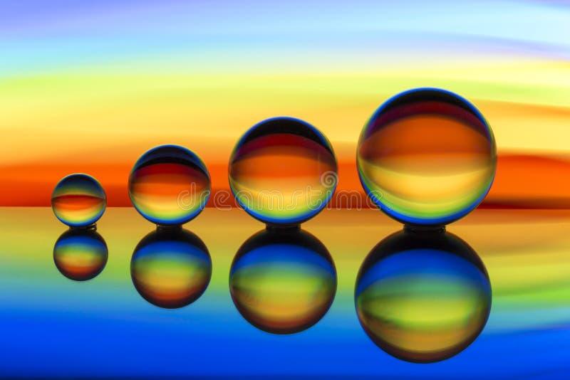 Cuatro bolas de cristal en fila con las rayas coloridas del color del arco iris detrás de ellas imágenes de archivo libres de regalías