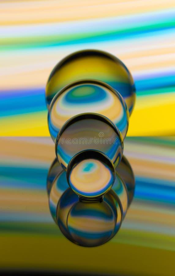Cuatro bolas de cristal de cristal en fila con un arco iris de la pintura ligera colorida detrás de ellos foto de archivo