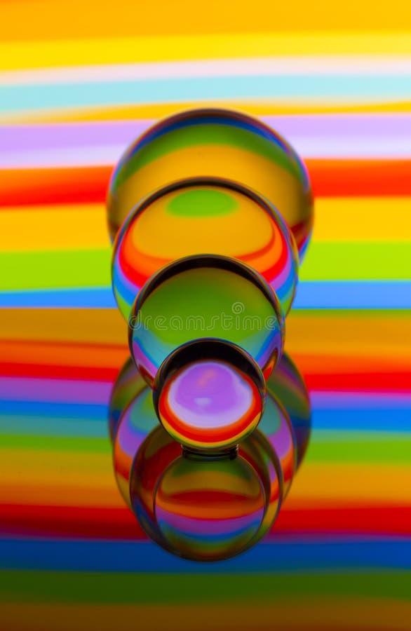 Cuatro bolas de cristal de cristal en fila con un arco iris de la pintura ligera colorida detrás de ellos imagen de archivo libre de regalías