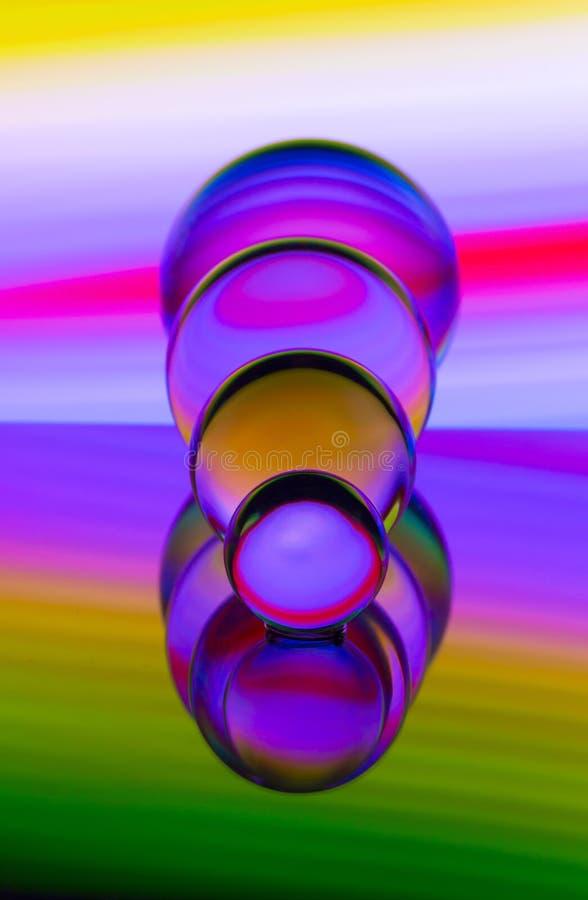 Cuatro bolas de cristal de cristal en fila con un arco iris de la pintura ligera colorida detrás de ellos imágenes de archivo libres de regalías
