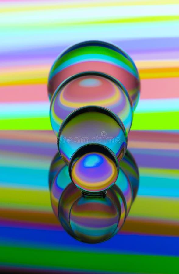Cuatro bolas de cristal de cristal en fila con un arco iris de la pintura ligera colorida detrás de ellos imagenes de archivo