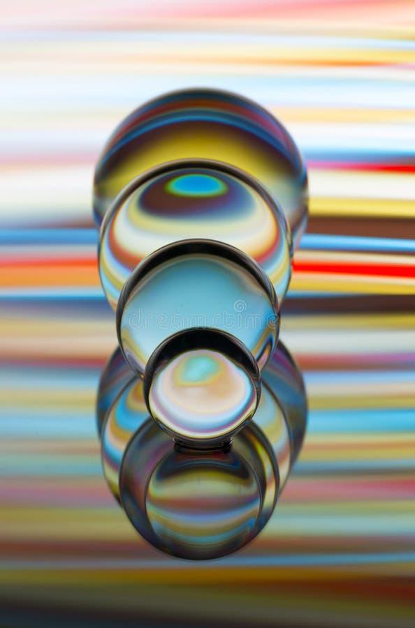 Cuatro bolas de cristal de cristal en fila con un arco iris de la pintura ligera colorida detrás de ellos fotografía de archivo