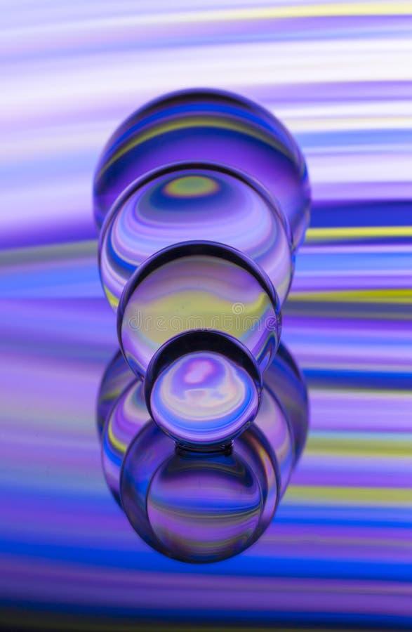 Cuatro bolas de cristal de cristal en fila con un arco iris de la pintura ligera colorida detrás de ellos fotografía de archivo libre de regalías
