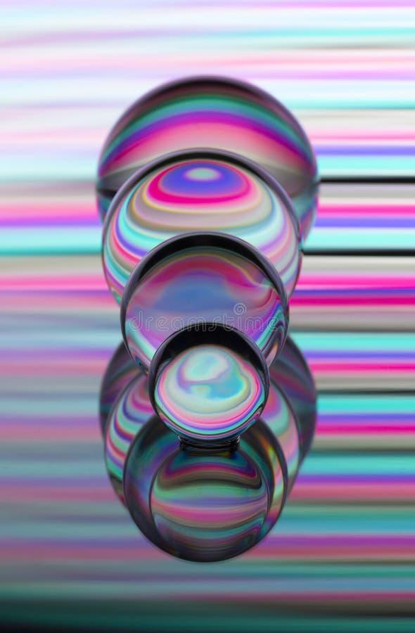 Cuatro bolas de cristal de cristal en fila con un arco iris de la pintura ligera colorida detrás de ellos fotos de archivo libres de regalías