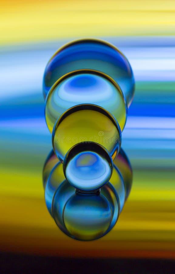 Cuatro bolas de cristal de cristal en fila con un arco iris de la pintura ligera colorida detrás de ellos foto de archivo libre de regalías