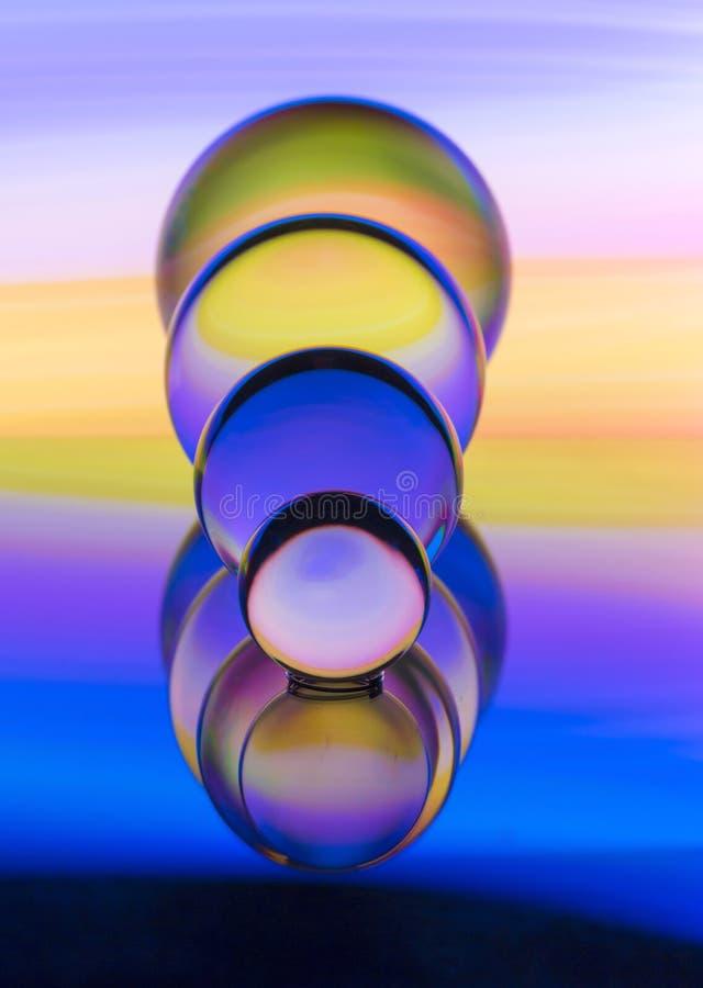 Cuatro bolas de cristal de cristal en fila con un arco iris de la pintura ligera colorida detrás de ellos imagen de archivo