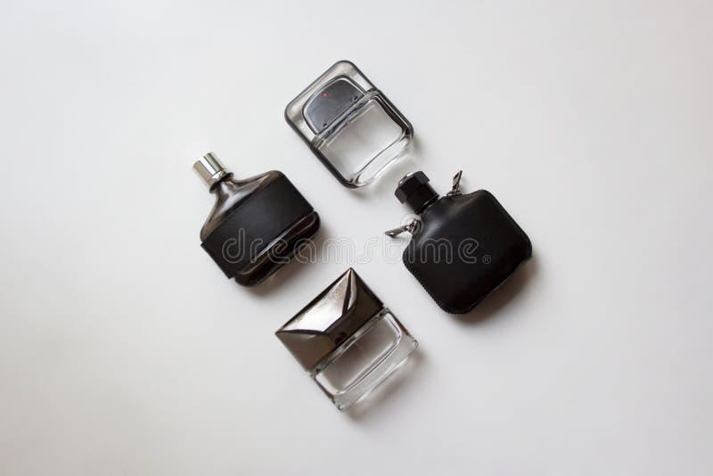 Cuatro botellas de perfume de cristal en el fondo blanco fotos de archivo