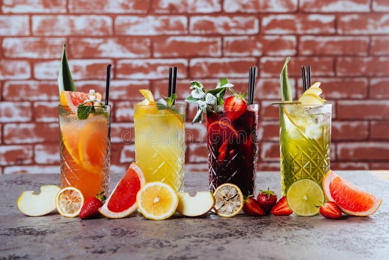 Cuatro cócteles en la tabla con las frutas imagen de archivo
