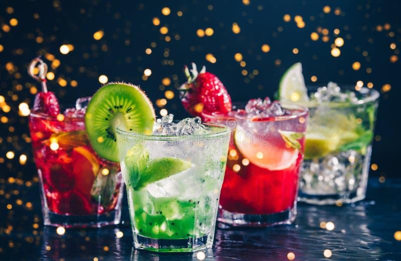Cuatro c?cteles alcoh?licos sabrosos coloridos en fila en el soporte de la barra Bokeh festivo del día de fiesta imágenes de archivo libres de regalías