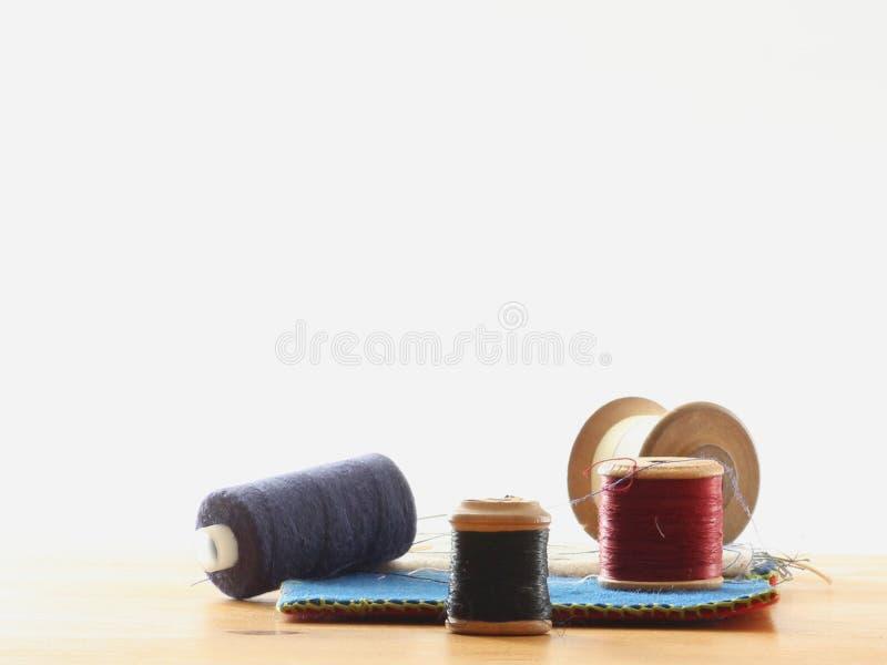 Cuatro carretes del algodón cerca para arriba en una tabla con un caso de la costura en un fondo blanco fotografía de archivo