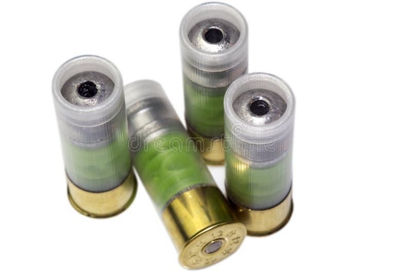 Cuatro 12 cartuchos de la bala de la escopeta de la caza del indicador aislados foto de archivo libre de regalías