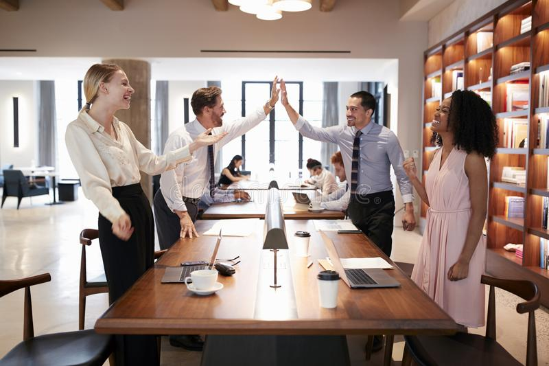 Cuatro colegas que celebran éxito en una oficina abierta del plan fotografía de archivo