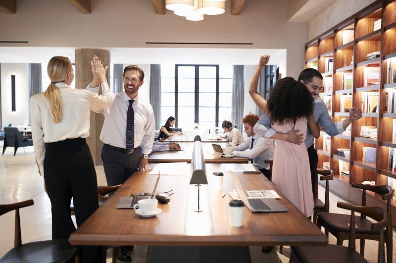 Cuatro colegas que celebran éxito en una oficina abierta del plan foto de archivo libre de regalías