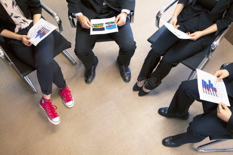 Cuatro compañeros de trabajo que celebran una reunión de negocios, opinión de alto ángulo imagen de archivo libre de regalías