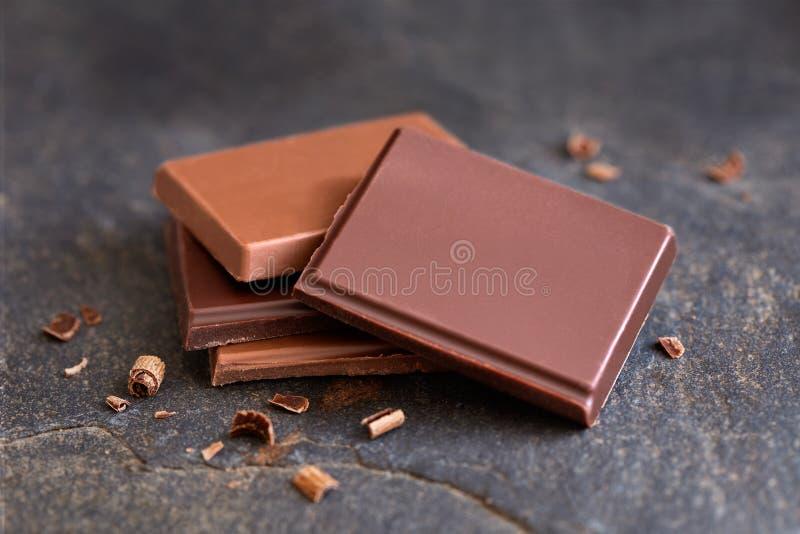 Cuatro cuadrados de oscuridad y de chocolate con leche aislados en pizarra gris Pequeños pedazos del chocolate Fondo de la falta  foto de archivo libre de regalías