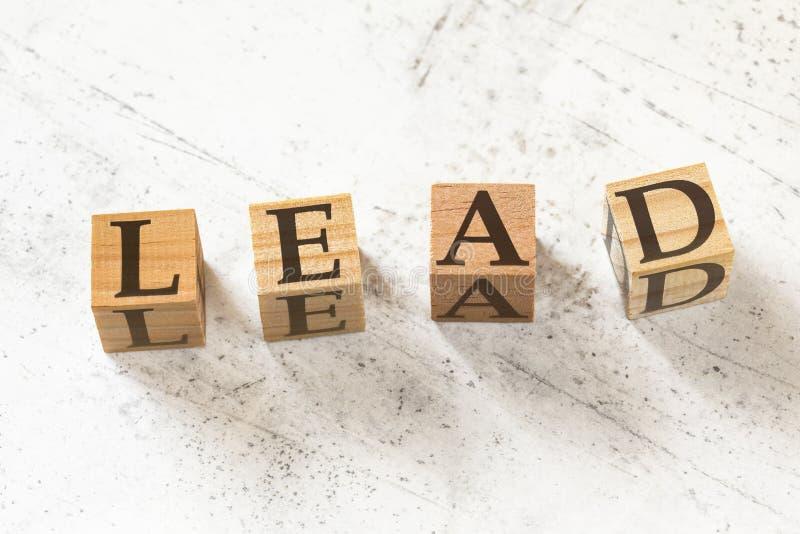 Cuatro cubos de madera con letras LEAD que significan Aprendizaje, Educación, Desarrollo de Acción en tablero blanco de trabajo imagen de archivo libre de regalías