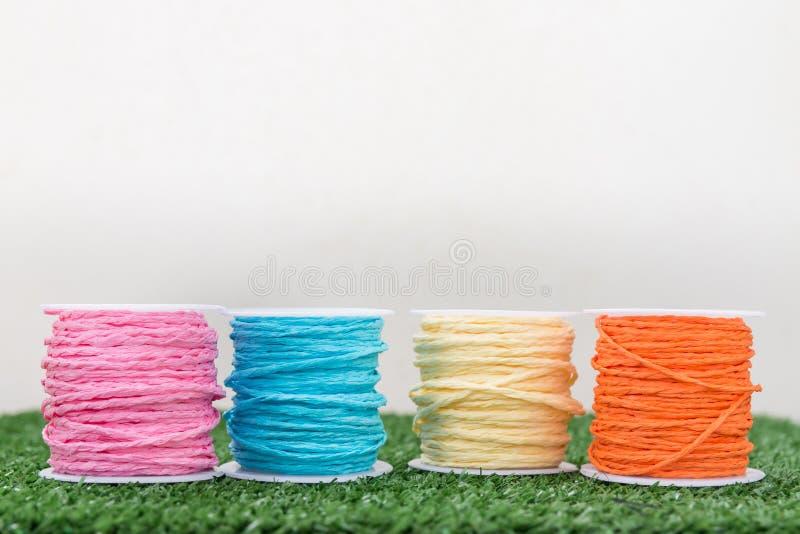 Cuatro del hilo colorido en hierba con el fondo blanco fotografía de archivo libre de regalías