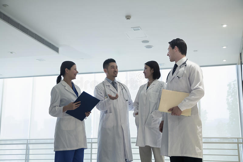 Cuatro doctores que se colocan, hablando, y sonriendo en el hospital fotos de archivo