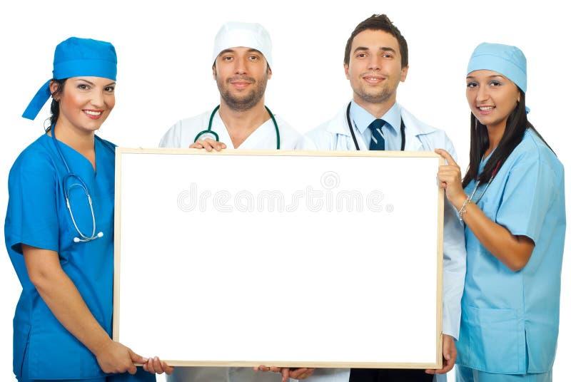 Cuatro doctores que sostienen la bandera en blanco imagen de archivo libre de regalías