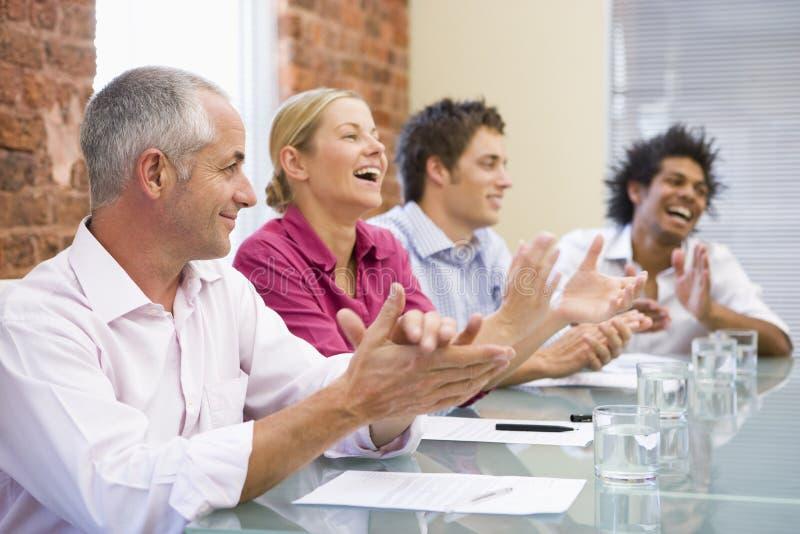 Cuatro empresarios en el aplauso de la sala de reunión fotos de archivo libres de regalías