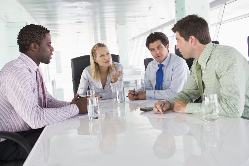 Cuatro empresarios en hablar de la sala de reunión imagen de archivo