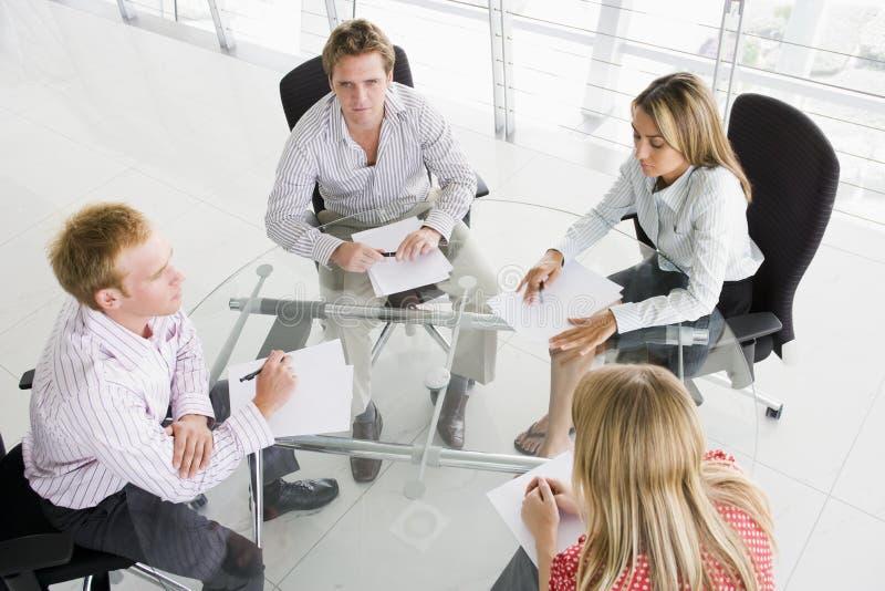 Cuatro empresarios en la sala de reunión con papeleo fotografía de archivo