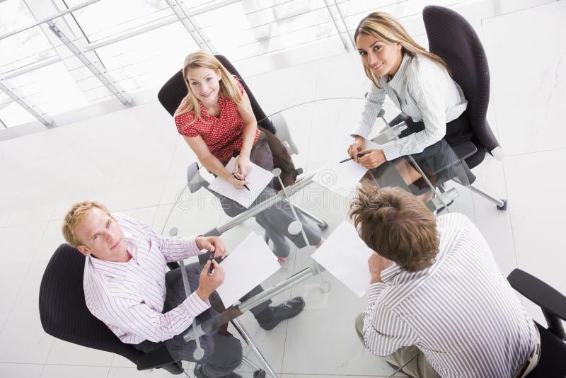 Cuatro empresarios en la sala de reunión con papeleo foto de archivo