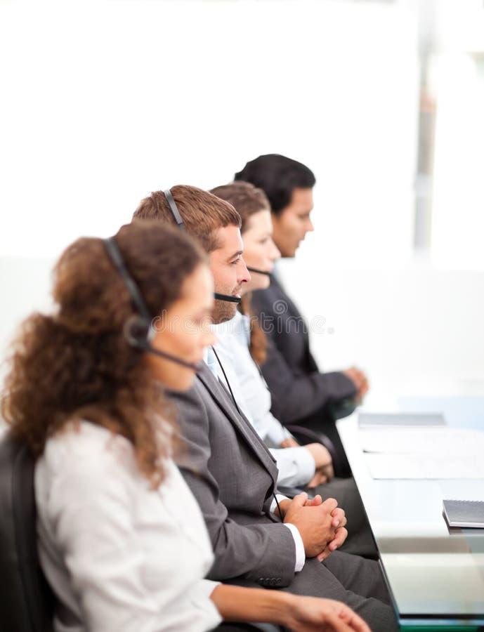 Cuatro empresarios en su escritorio en un centro de llamada imagen de archivo