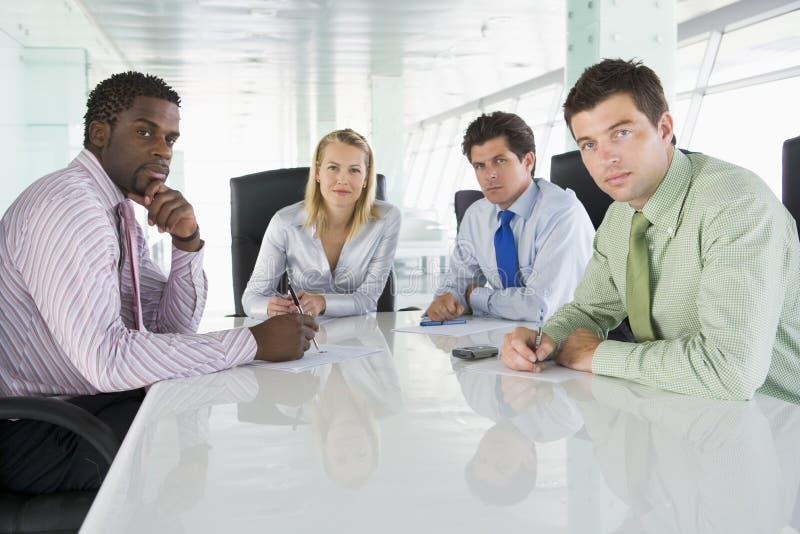 Cuatro empresarios en una sala de reunión imagen de archivo libre de regalías