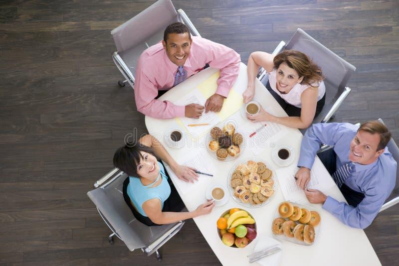 Cuatro empresarios que comen en el vector de la sala de reunión imágenes de archivo libres de regalías