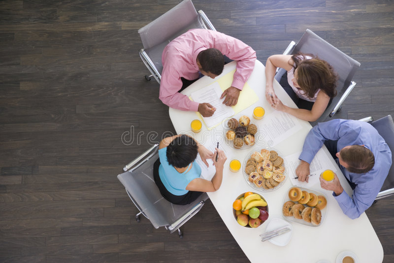 Cuatro empresarios que comen en el vector de la sala de reunión imagen de archivo