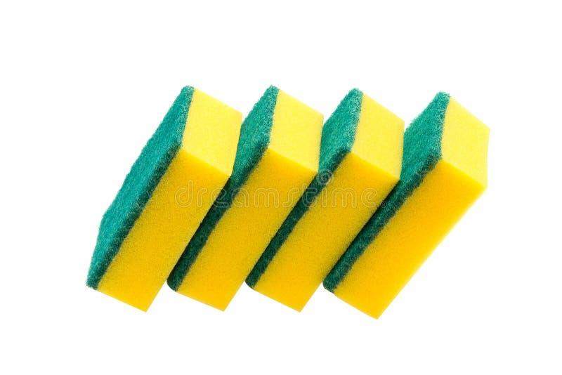 Cuatro esponjas amarillas para los platos que se lavan en el fondo blanco fotos de archivo