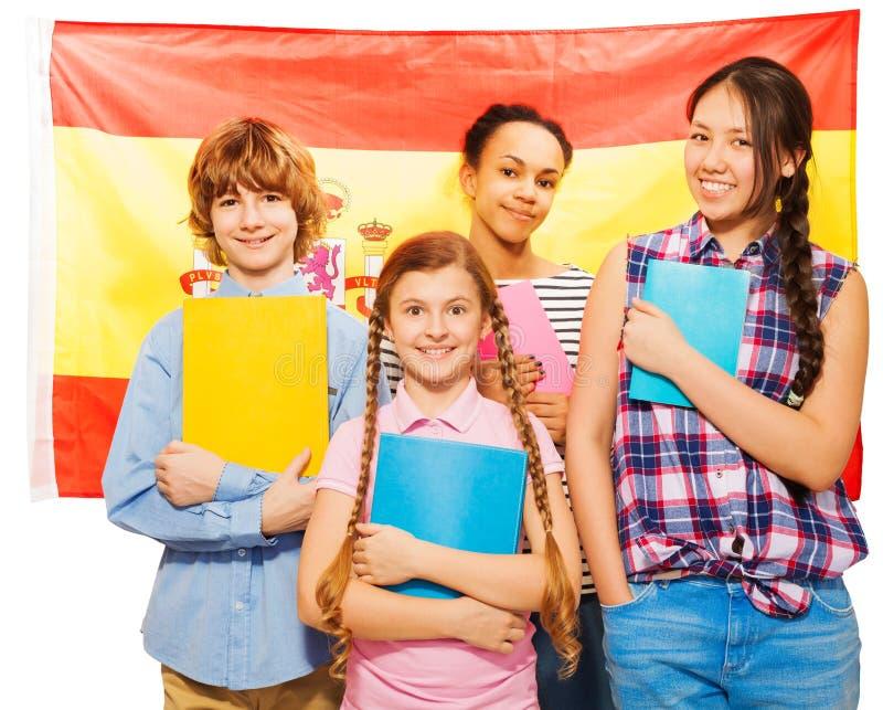 Cuatro estudiantes felices que se colocan con la bandera española foto de archivo