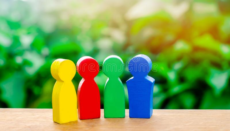 Cuatro figuras coloridas de hablar de la gente Cooperación internacional, proyecto común El el concepto de cooperación y mutuo fotos de archivo
