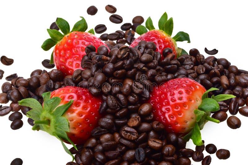 Cuatro fresas maduras del verano con las hojas verdes claras, asperjadas con los granos de café asados imagenes de archivo