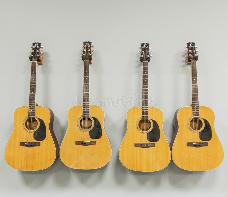 Cuatro guitarras acústicas que cuelgan en una pared blanca imagenes de archivo